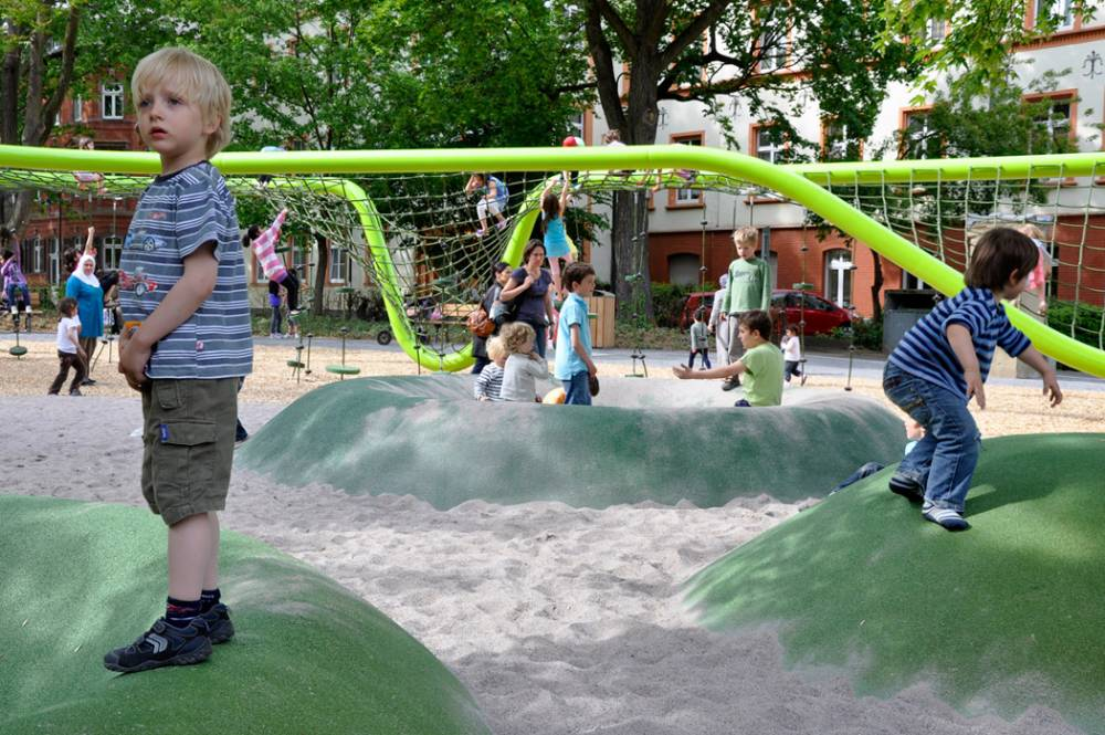 Kids playing on the poured rubber mounds