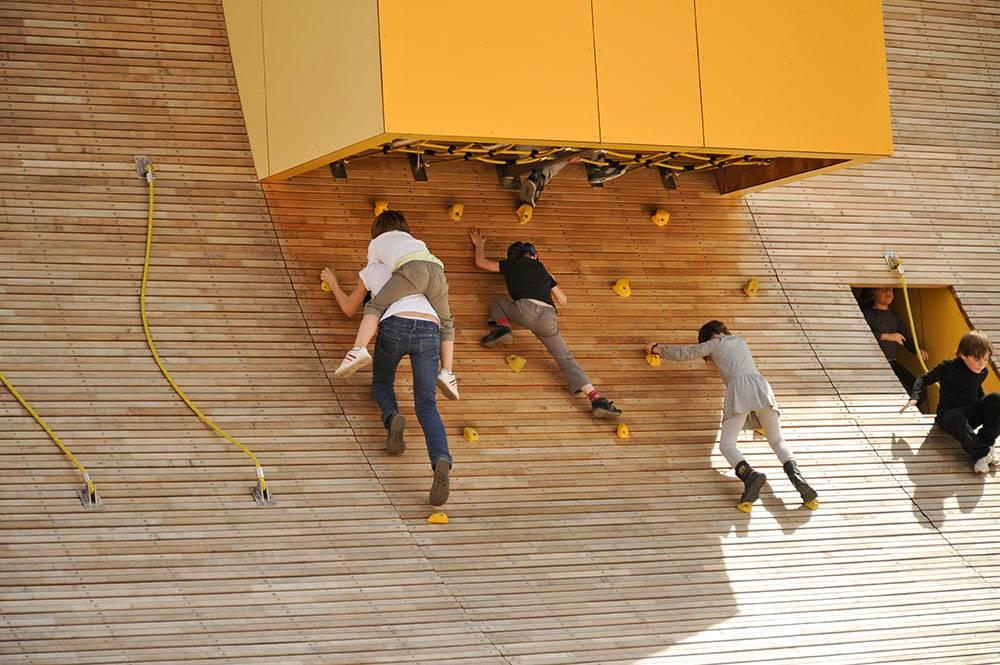 Children scrambling up climbing holds