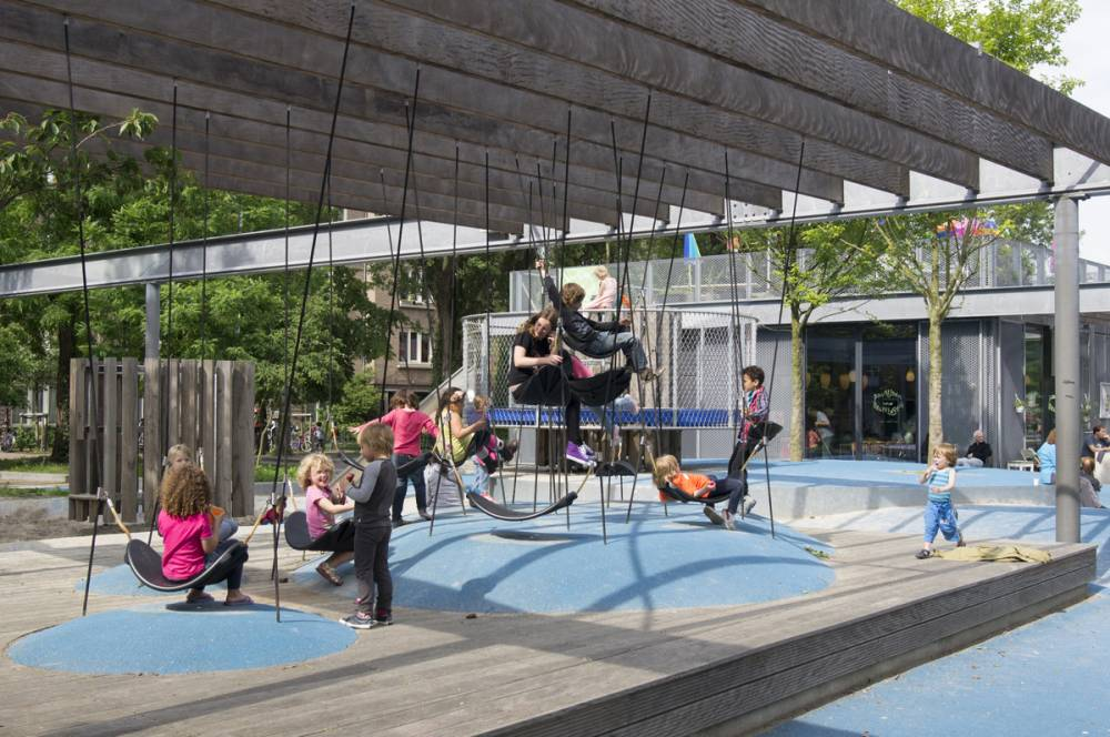 Children playing on tethered rope seats and rubber mounds