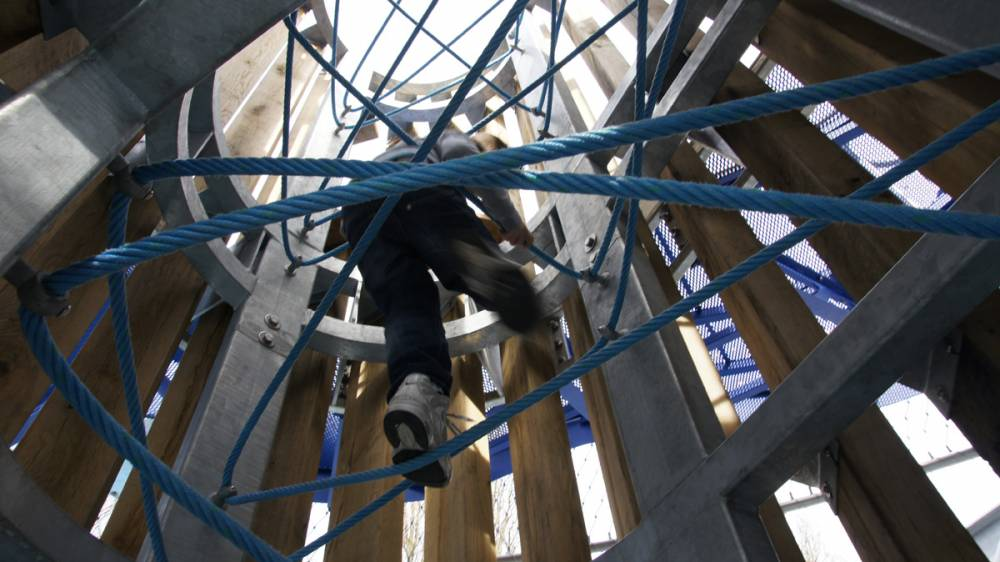 Climbing up ropes inside tower
