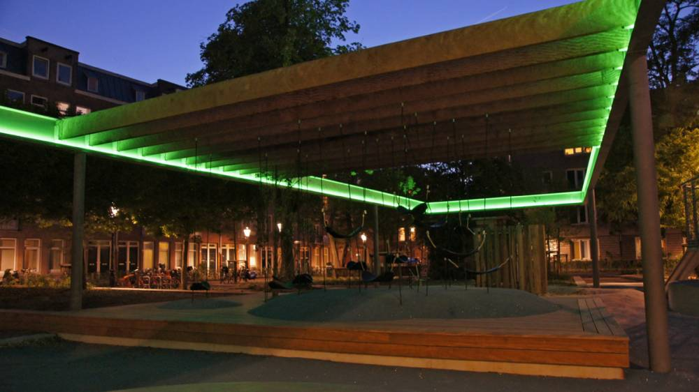 Green tube lighting illuminates the park at night