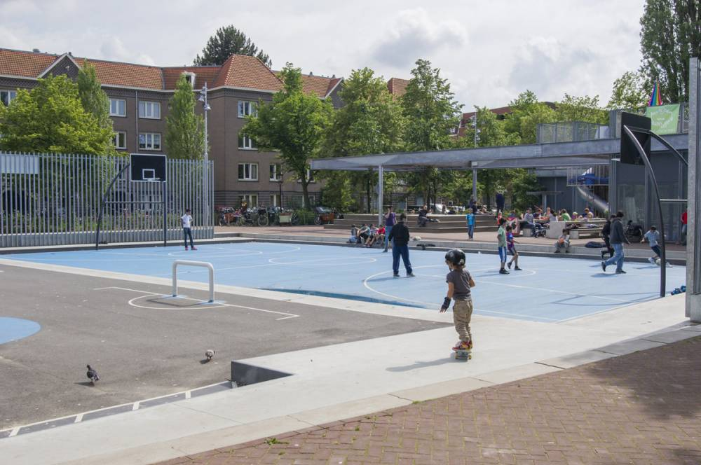 Children play on the blue sport court