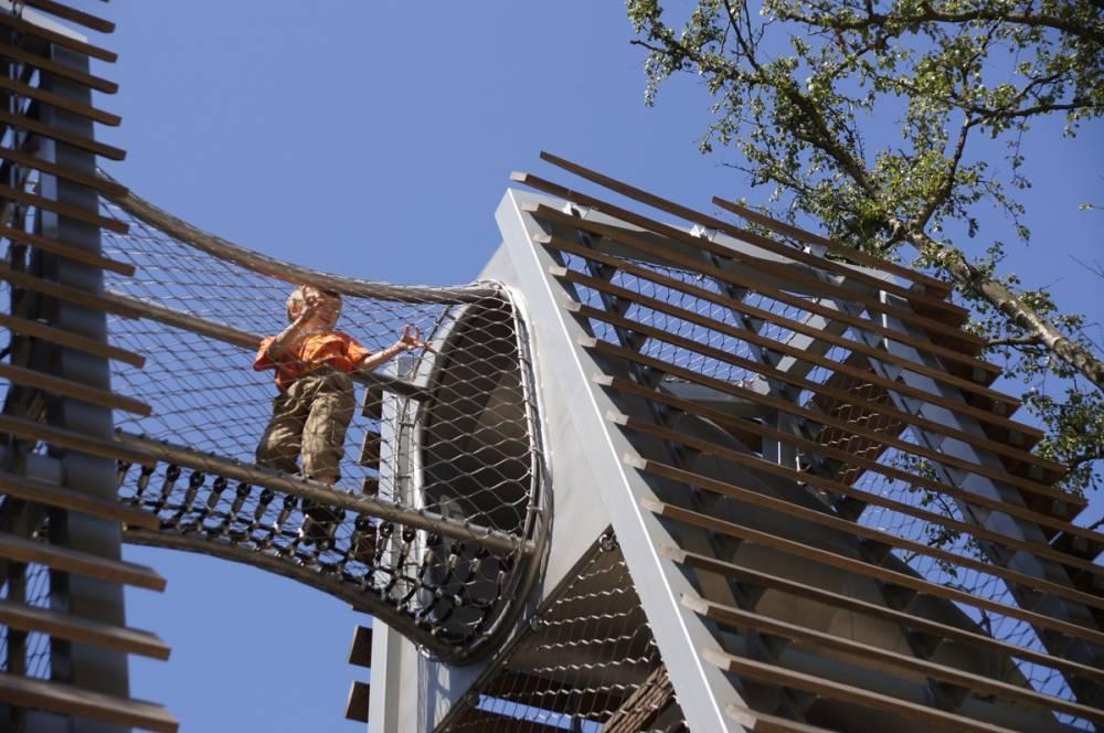 Child walking across net bridge between towers