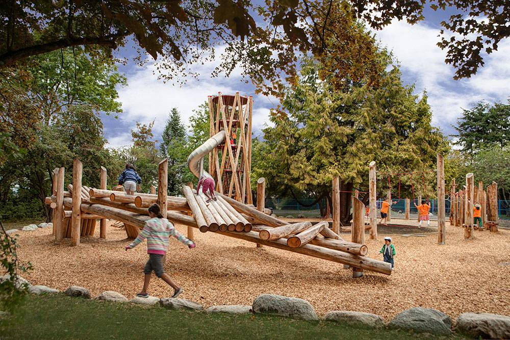 Children play on wood climbing structure
