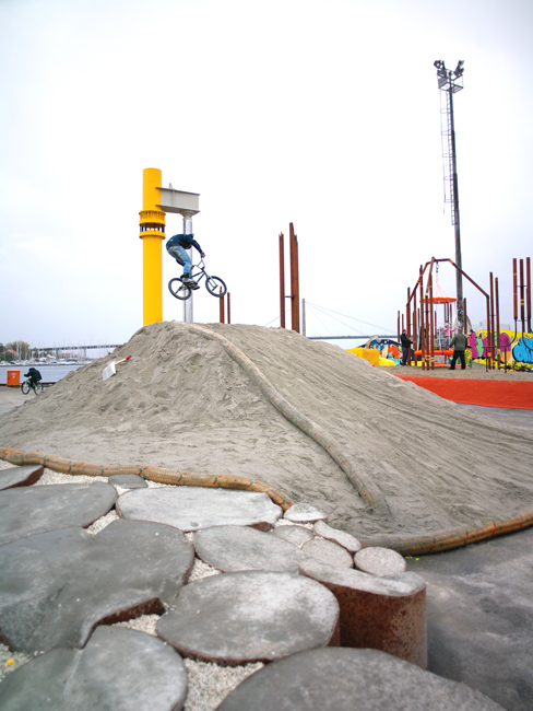 A BMX ride gets airborne above sand mound