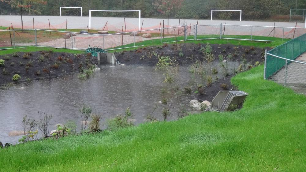 Retention pond collects rainwater, with a surrounding chainlink fence for safety
