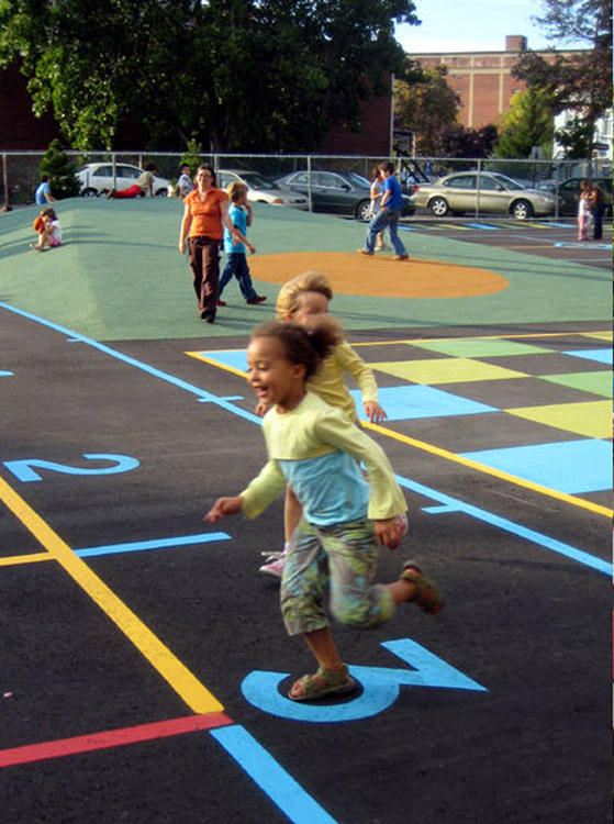 Children playing on painted asphalt with mound in the background