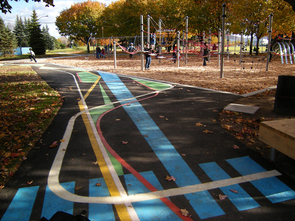 Abstract painted patterns on asphalt with playground beyond