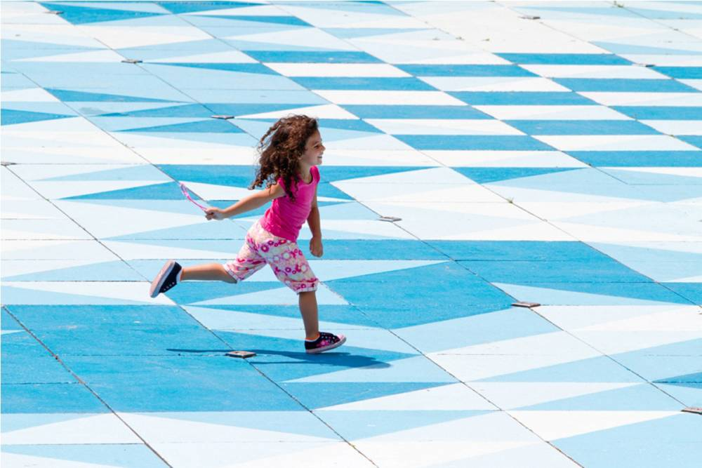 Girl running across the painted pavers