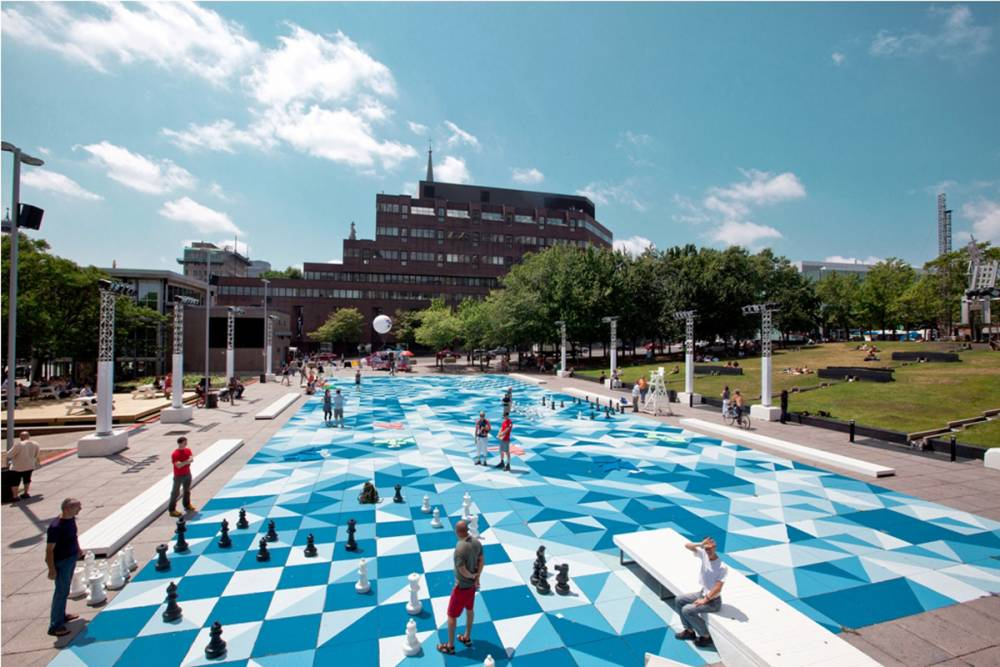 "A game of giant chess takes place beside the ""diving board"" bench"
