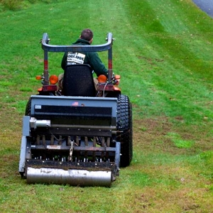 Rolling an aerating machine over compacted lawn