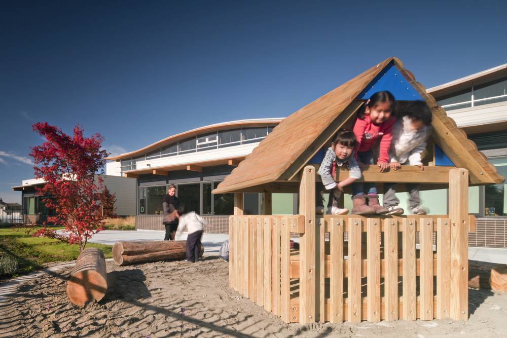 Small wood playhouse in sand pit