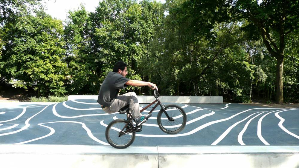 Popping a wheelie on one of the long concrete benches