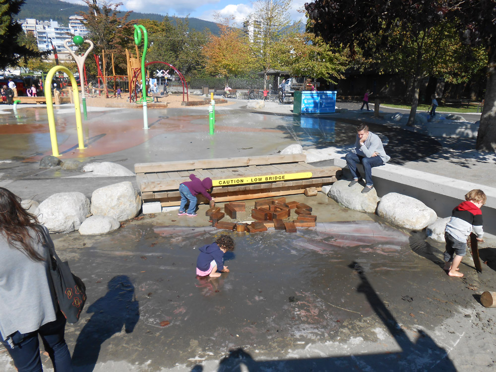 Small children play in the water beside the splash pad