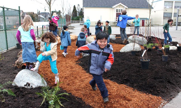 Children playing on the mulch during the planting phase