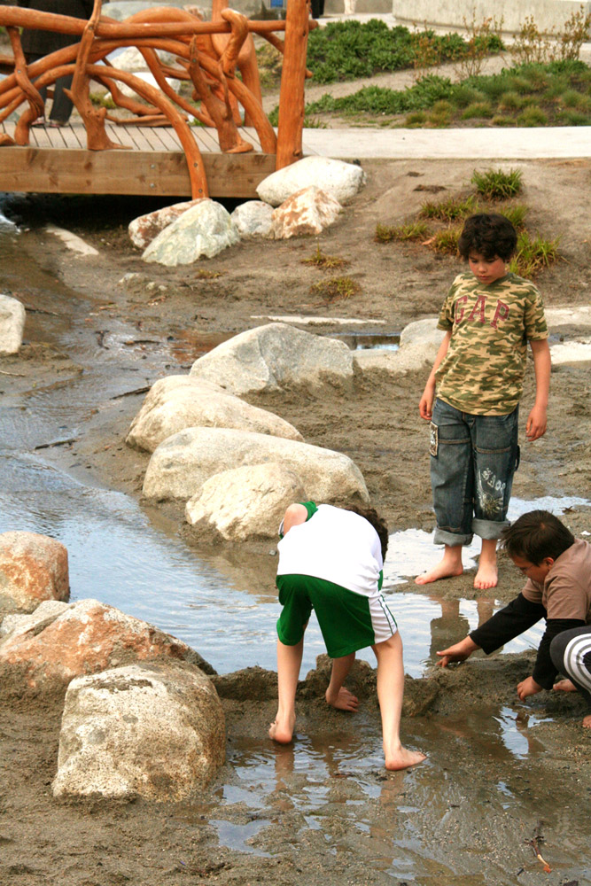 Children constructing a sand dam in a water channel