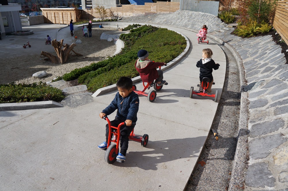 Children tricycle up and down the ramp