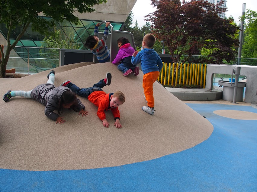 Children play on rubber mound with an integrated slide