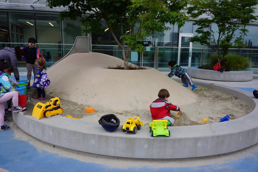 Playing in sand pit beside rubber mound